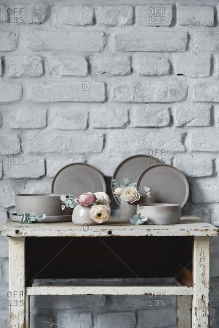 Handmade ceramic plate and bowl set with sugar flowers for cake decorating on a rustic table