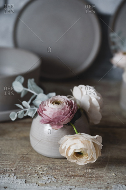 Beautiful sugar flowers inside of a handmade ceramic cup on a rustic table