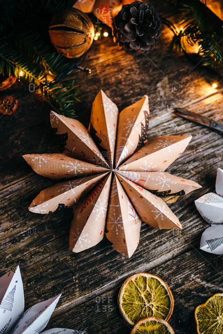 Close up of star shaped Christmas paper decoration on wooden surface
