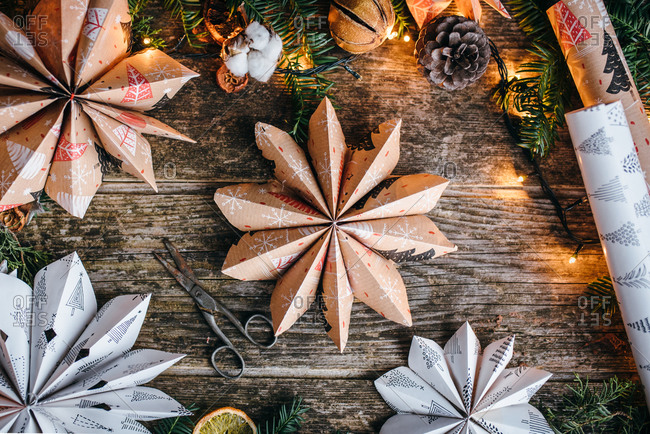 Star shaped Christmas paper decoration on wooden surface with lights and dried fruit