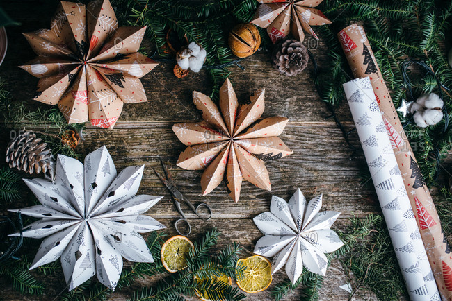 Star shaped Christmas paper decoration on wooden surface surrounded by pine branches and ornaments