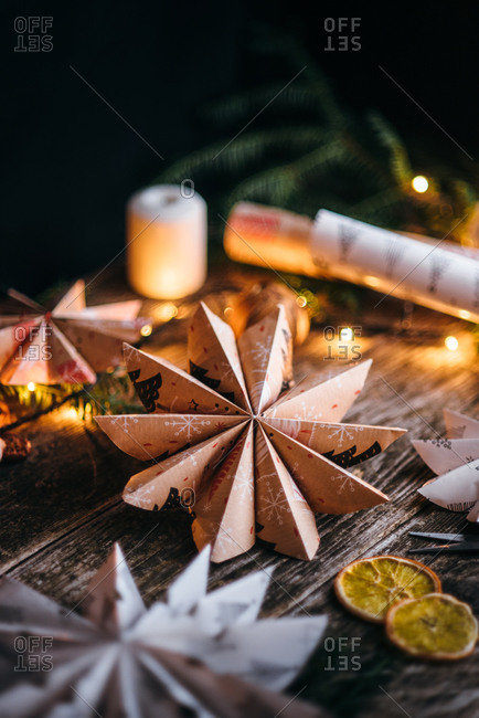 Close up of star shaped Christmas paper decoration on wooden surface surrounded by lights and dried fruit