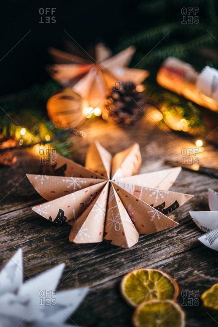 Handmade star shaped Christmas paper decoration on wooden surface surrounded by lights and dried fruit