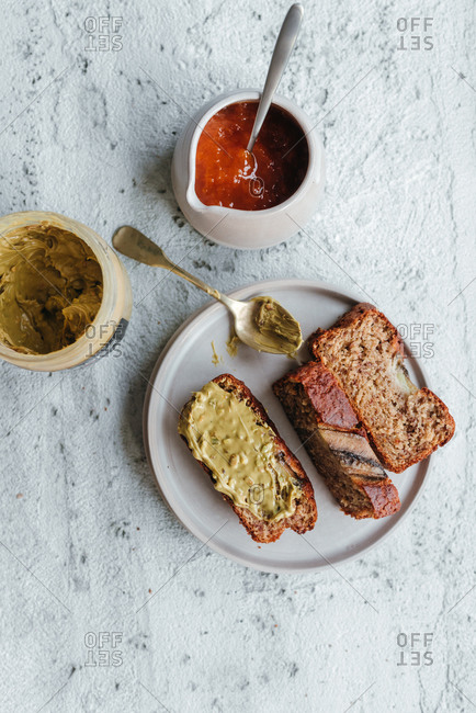 Slice of banana bread with no added sugar served on plate next to apricot jam and pistachio cream