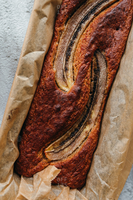 Close up of a whole loaf of banana bread with no added sugar in baking pan with parchment paper