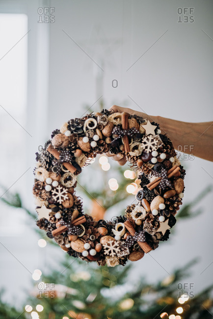 Hand holding a Christmas wreath decoration made from natural materials in front of a tree