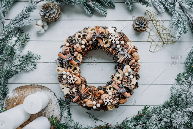 Christmas wreath decoration made from natural materials on white wooden background
