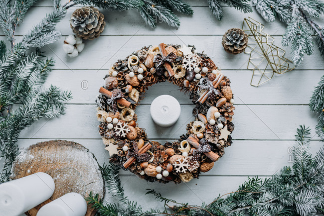 Candle in the center of a Christmas wreath decoration made from natural materials on white wooden background