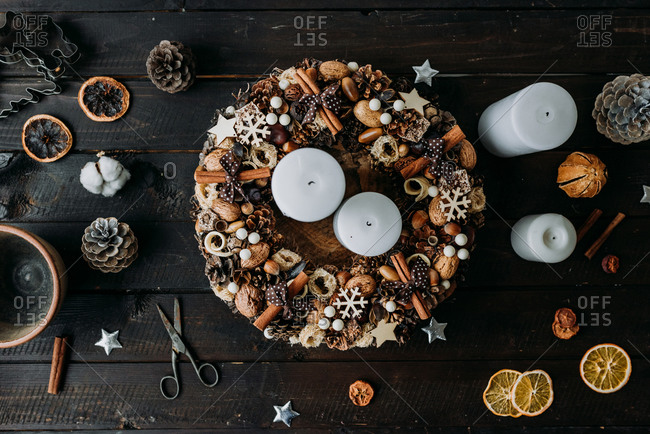 Christmas wreath decoration made from natural materials such as cinnamon and nuts on rustic wooden surface