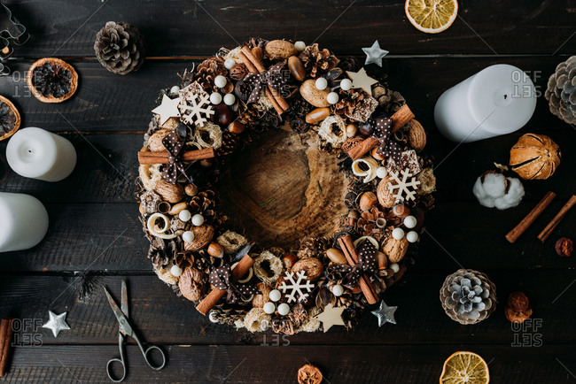Top view of a Christmas wreath decoration made from natural materials such as cinnamon and nuts on rustic wooden surface