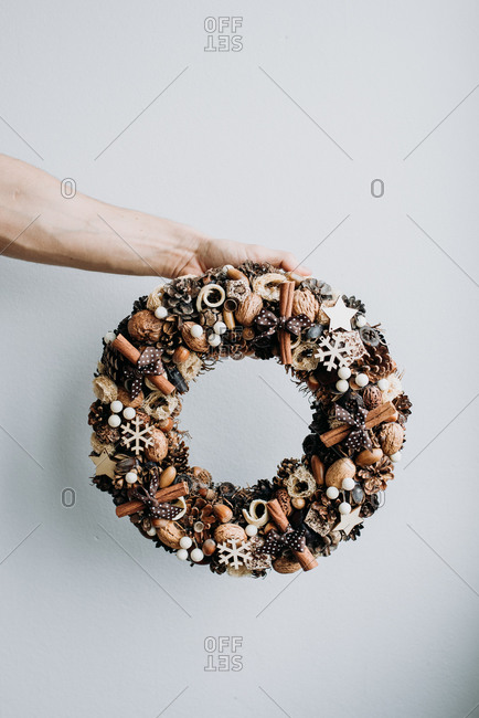 Christmas wreath decoration made from natural materials held in front of white background