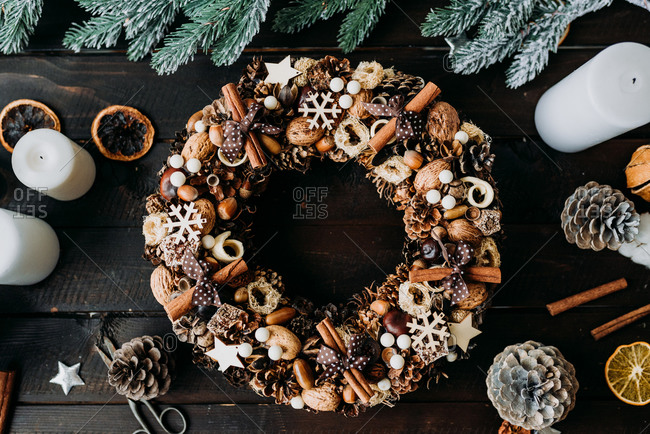 Christmas wreath decoration made from natural materials on rustic wooden surface