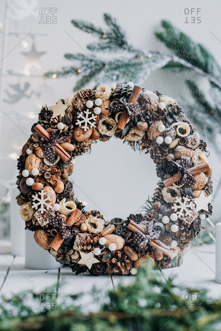 Christmas wreath decoration made from natural materials in front of white background with pine branch