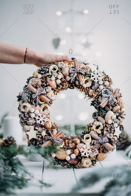 Hand holding a beautiful Christmas wreath made from natural materials like cinnamon and nuts