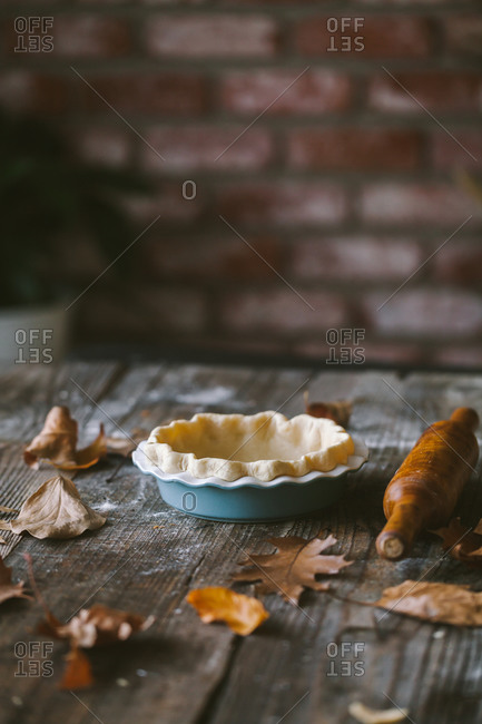 Empty pie crust on rustic table with fallen autumn leaves and rolling pin