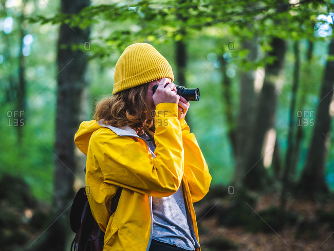 Side view of unrecognizable female traveler in yellow raincoat and hat taking picture on photo camera while exploring nature in woods