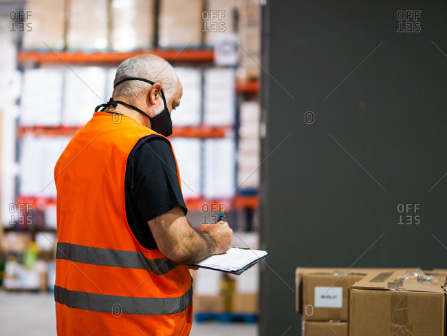 Back view adult worker wearing uniform and protective face mask writing on clipboard while working in spacious storehouse