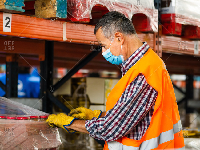 Side view adult professional storehouse specialist in uniform and protective face mask wrapping big carton box while standing near stacks