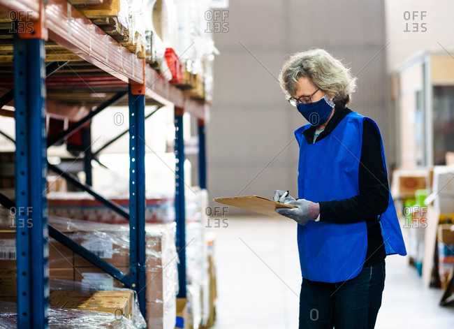 Side view focused female worker in blue vest and face mask taking notes in clipboard while standing near stacks in warehouse