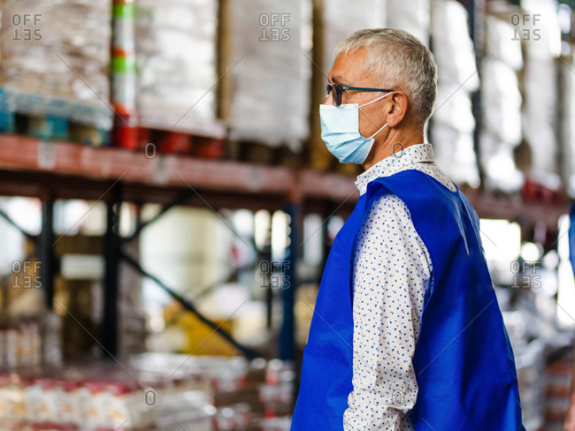 Side view adult gray haired male worker wearing blue vest and protective mask standing near stacks in modern storehouse