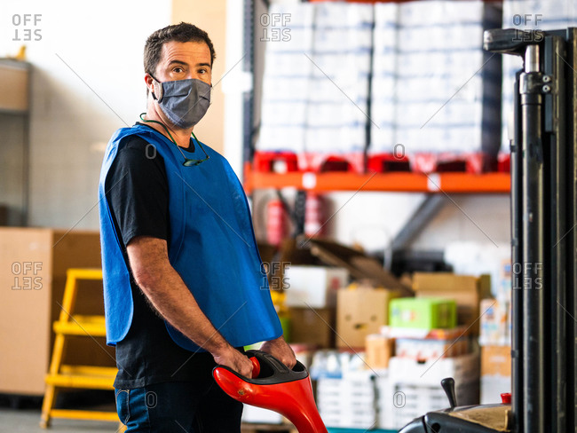 Focused adult male worker wearing high visibility vest and face mask holding trolley cart handle and looking at camera while working in contemporary storehouse