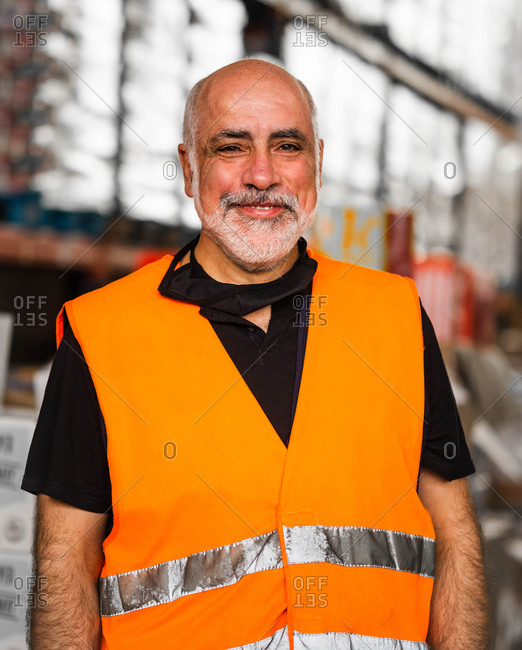 Serious adult male worker wearing orange high visibility vest standing near warehouse racks and looking at camera