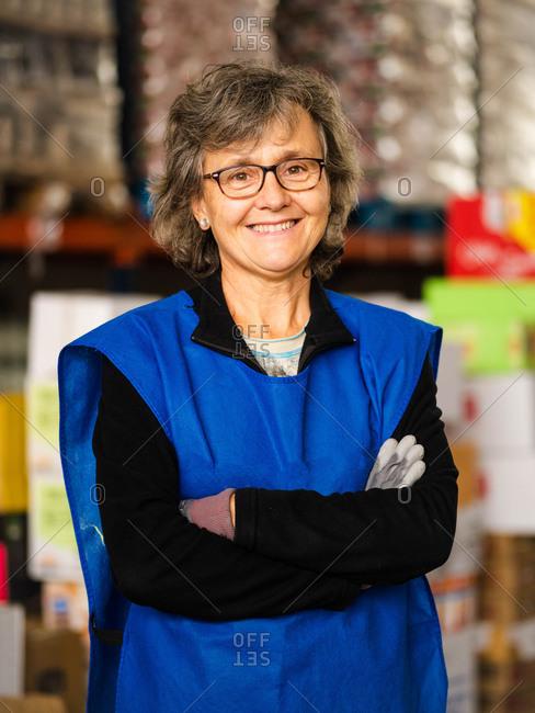 Smiling mature female specialist wearing blue vest and gloves standing with arms crossed against racks in contemporary storehouse and looking at camera