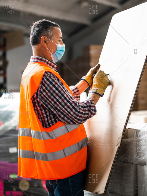 Side view serious adult male worker in high visibility vest and protective face mask writing on big carton board in modern storehouse