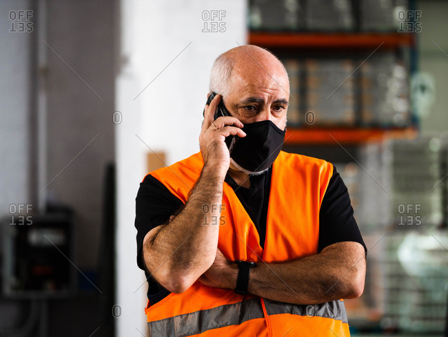 Serious adult male manager in uniform and protective mask standing with arms crossed near warehouse autoloader and having conversation on mobile phone