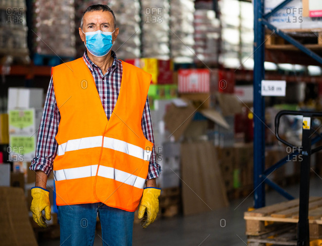 Serious adult male worker wearing orange high visibility vest and medical mask standing near warehouse racks and looking at camera