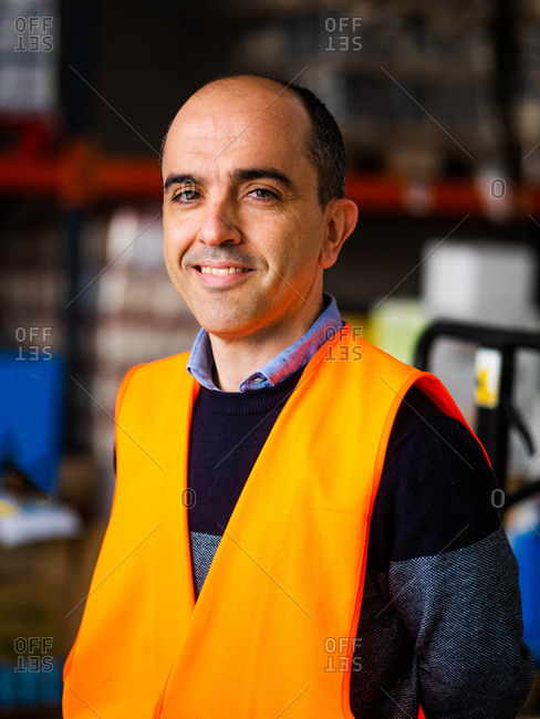 Happy adult male worker wearing orange high visibility vest standing near warehouse racks and looking at camera