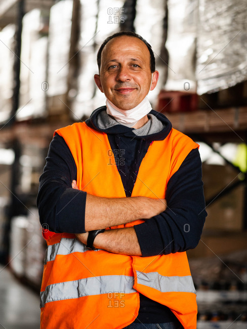 Happy male worker wearing blue vest and lowered protective mask standing against warehouse racks and looking at camera calmly