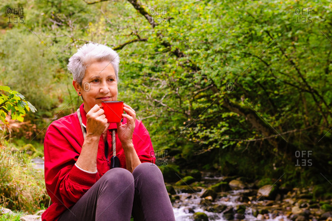 Contemplative elderly female tourist drinking water near Casano river while resting on stone and looking away