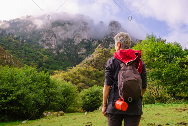 Back view of unrecognizable female traveler with rucksack standing on green meadow while travelling in Asturias
