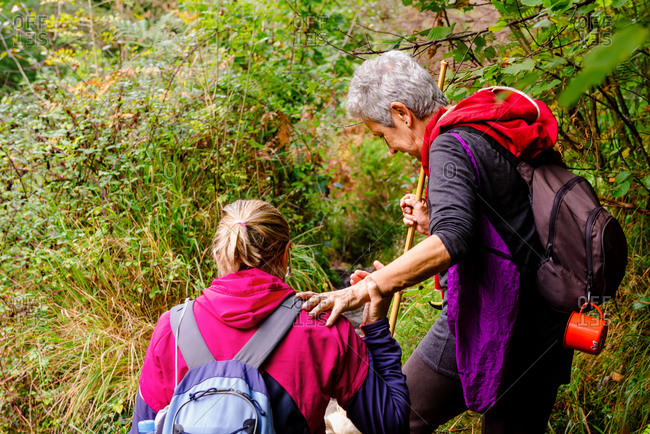 Unrecognizable female hiker helping elderly partner with backpack while travelling together near greenery plants in Asturias