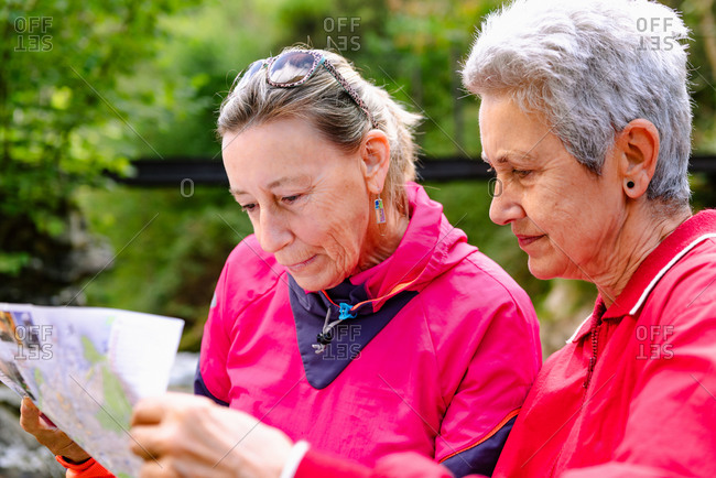 Senior female hikers watching paper map on mountain behind Casano river in Spain