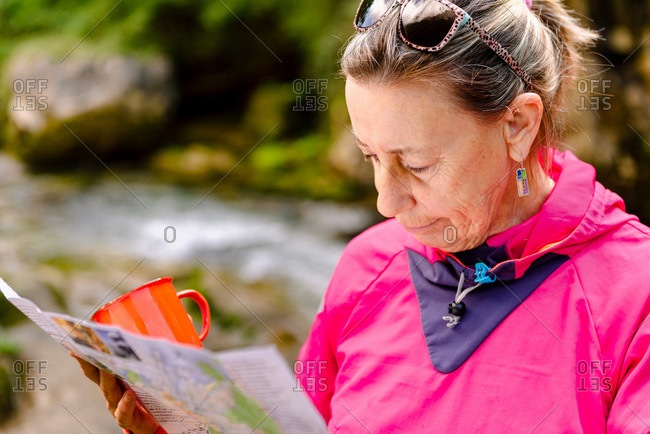 Senior female hiker watching paper map on mountain behind Casano river in Spain