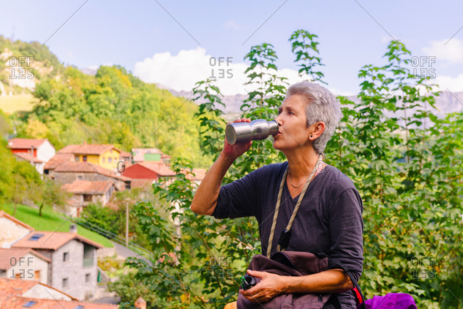 Middle aged female traveler drinking hot drink from thermos near green mounts and houses while looking away