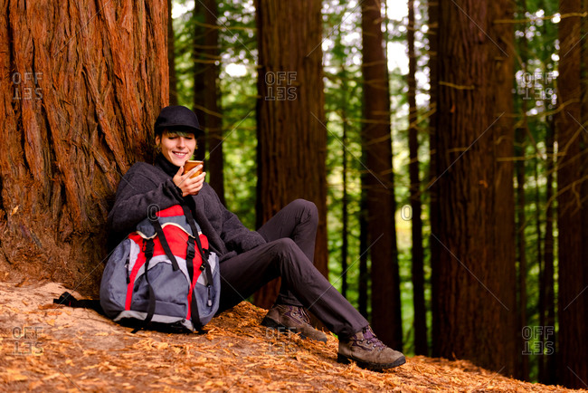 Cheerful tourist with backpack leaning on tree and browsing smartphone while relaxing in Monte Cabezon Natural Monument of Sequoias during holiday