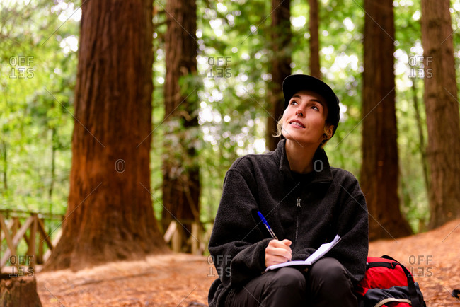 Female explorer sitting in woods and writing in notebook while enjoying vacation in Monte Cabezon Natural Monument of Sequoias in Cantabria