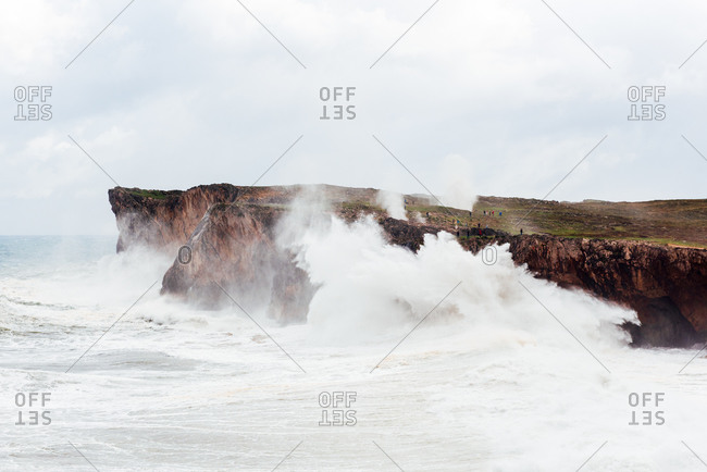 Spectacular scenery of foamy sea waving over rough rocky cliff on sunny day in Bufones de Llames Pria in Spain