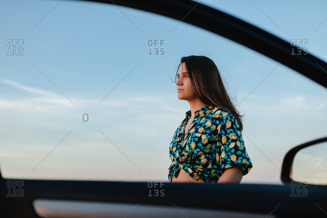 Young charming female in trendy wear with ornament looking away near auto door under blue cloudy sky