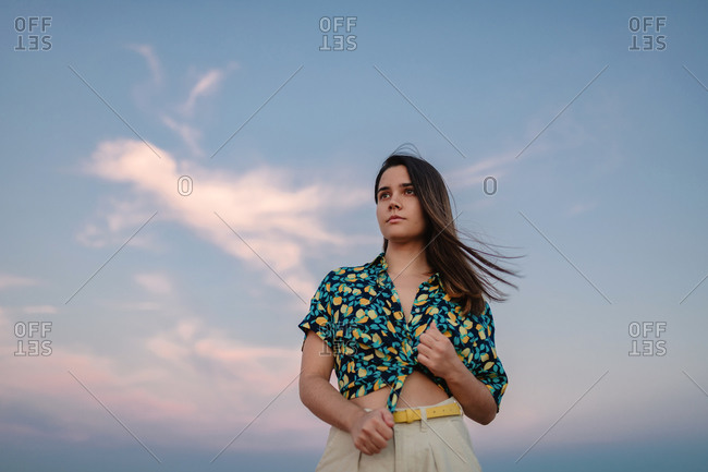 Low angle of young stylish mindful female under sky at sundown and looking away
