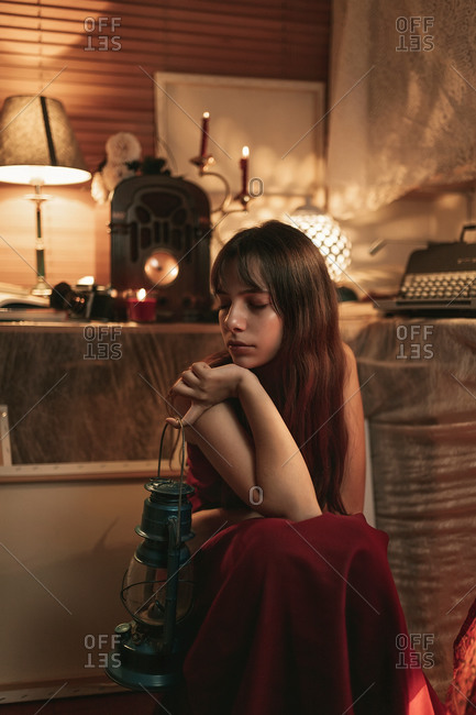 Peaceful female in red dress sitting in cozy room with old fashioned kerosene lantern while enjoying evening with eyes closed