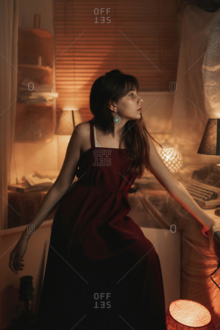 Peaceful female in red dress sitting in cozy room while enjoying evening and looking away