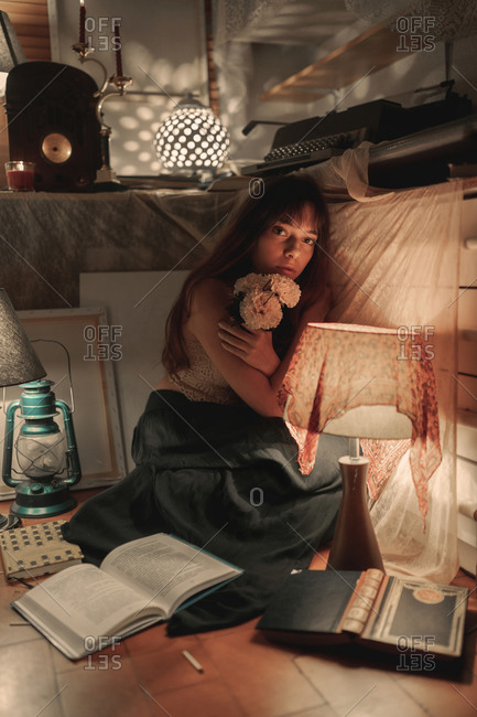 Young charming female embracing bouquet of blossoming delicate flowers looking at camera on cozy room with dim orange light