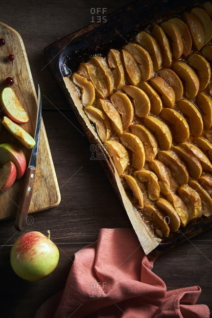 From above of sliced baked apples on baking tray placed on wooden table with fresh fruits