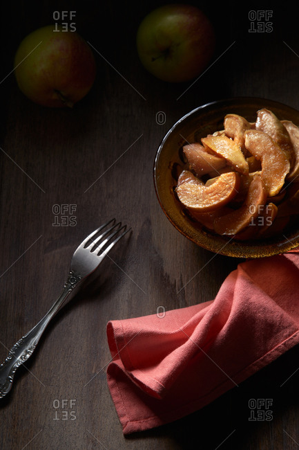 From above of bowl with delicious sweet sliced baked apples served on table with fork and napkin