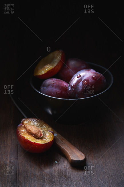 Still life composition with bowl with ripe aromatic juicy plums with water drops arranged on wooden table with knife and halved fruit