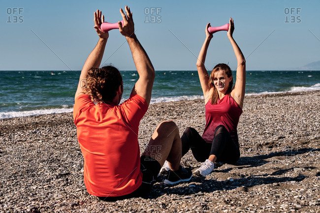 Sportive couple doing exercises with dumbbells while sitting at seaside on sunny day and looking at each other